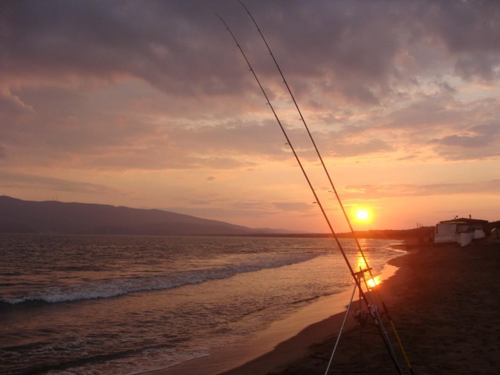 foto di un tramonto con in primo piano le mie canne da surfcasting
